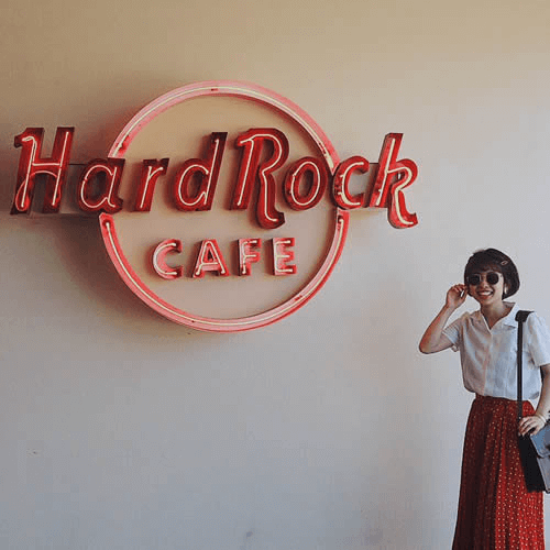 Customer infront of Hard Rock Cafe Logo
